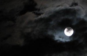 The moon shining through the clouds