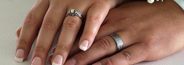 A closeup of a bride and groom's hands showing their wedding rings