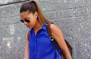 A young woman in a blue blouse leaving an office building