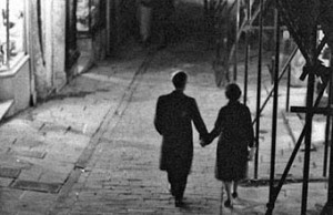 A couple walking down a cobblestone alley at night