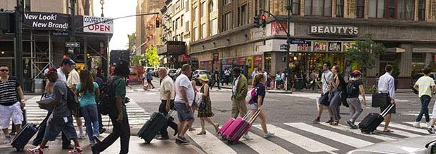 People crossing the street at a busy intersection in New York City