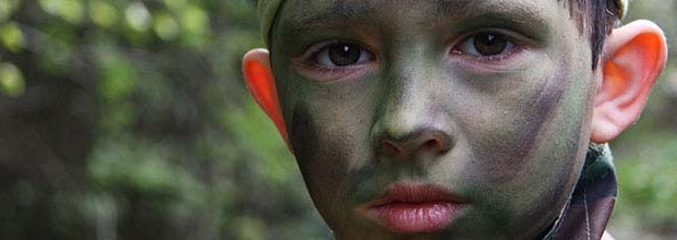 Closeup of a young boy in camouflage makeup in a forest